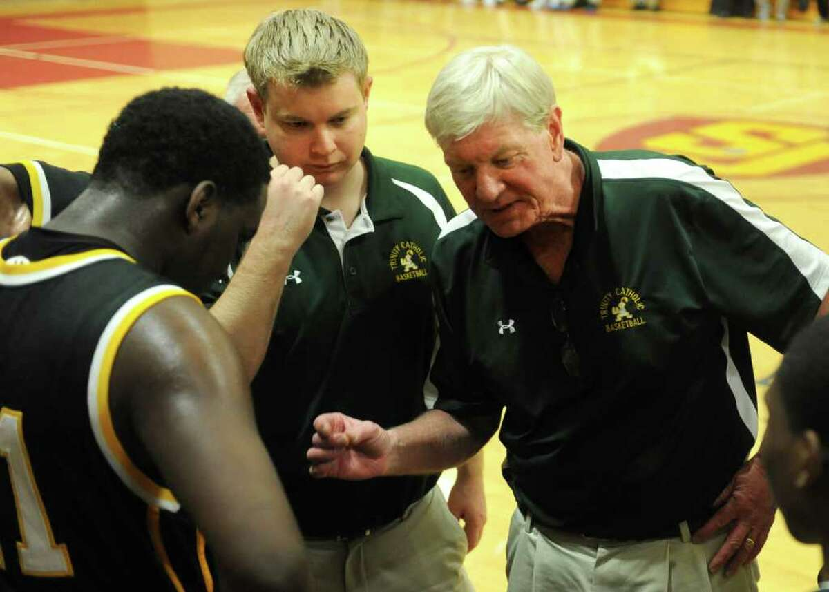 Trinity Catholic's coach Mike Walsh talks to his team in between quarters during Tuesday's game between Trinity and St. Joseph in Trumbull on December 21, 2010.