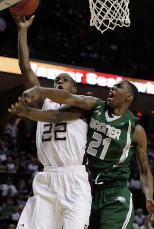 Texas A&M forward Khris Middleton is fouled by Wagner forward Orlando Parker during the first half of Tuesday's game in College Station. Photo: Pat Sullivan/Associated Press