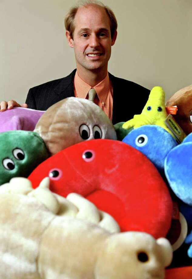 In this Nov. 24, 2010 photo, Drew Oliver, owner of Giant Microbes, displays a few of his creations in his Stamford, Conn. offices. The onetime Harvard Lampoon editor turned a sense of humor into a growing business of stuffed toy germs. Once found mostly in pediatricians' offices and the labs of off-kilter university professors, his cuddly stuffed germs has spawned a Facebook fan club and subculture of eager collectors. (AP Photo/Craig Ruttle) Photo: Craig Ruttle, AP / AP2010