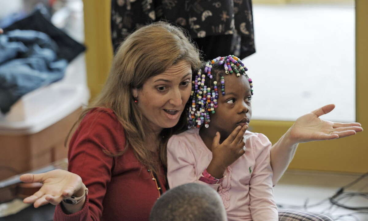 Tina Moore entertains Charnea Gause at the Sheridan Prep Elementary School in Albany during a holiday songfest on Tuesday, Dec. 21, 2010. (Skip Dickstein / Times Union)