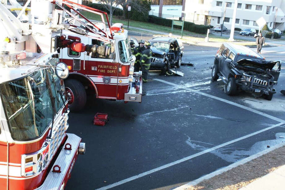 Fairfield firefighters, police perosnnel and American Medical Response technicians work at the scene of a two-car accident at Black Rock Turnpike and Burroughs Road. Photo: Contributed Photo / Fairfield Citizen contributed