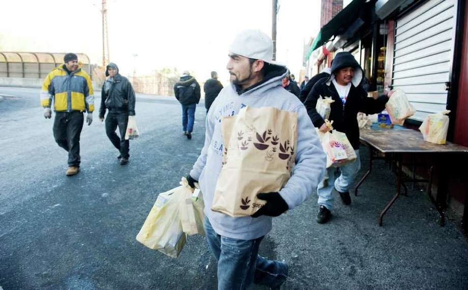Louis Reyes carries bags of groceries as a group of day laborers receive food donations collected by Brien McMahon students involved in the Peace Project in Norwalk, Conn on Wednesday December 22, 2010. Photo: Kathleen O'Rourke / Stamford Advocate