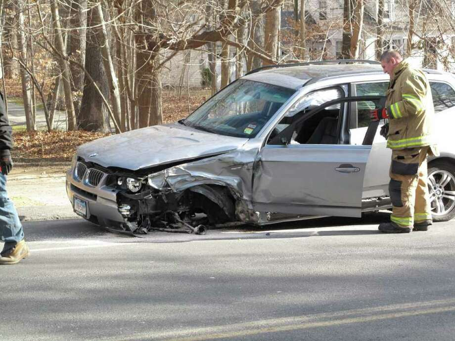 Firemen and Police officers examine the vehicle. Photo: Contributed Photo / New Canaan News
