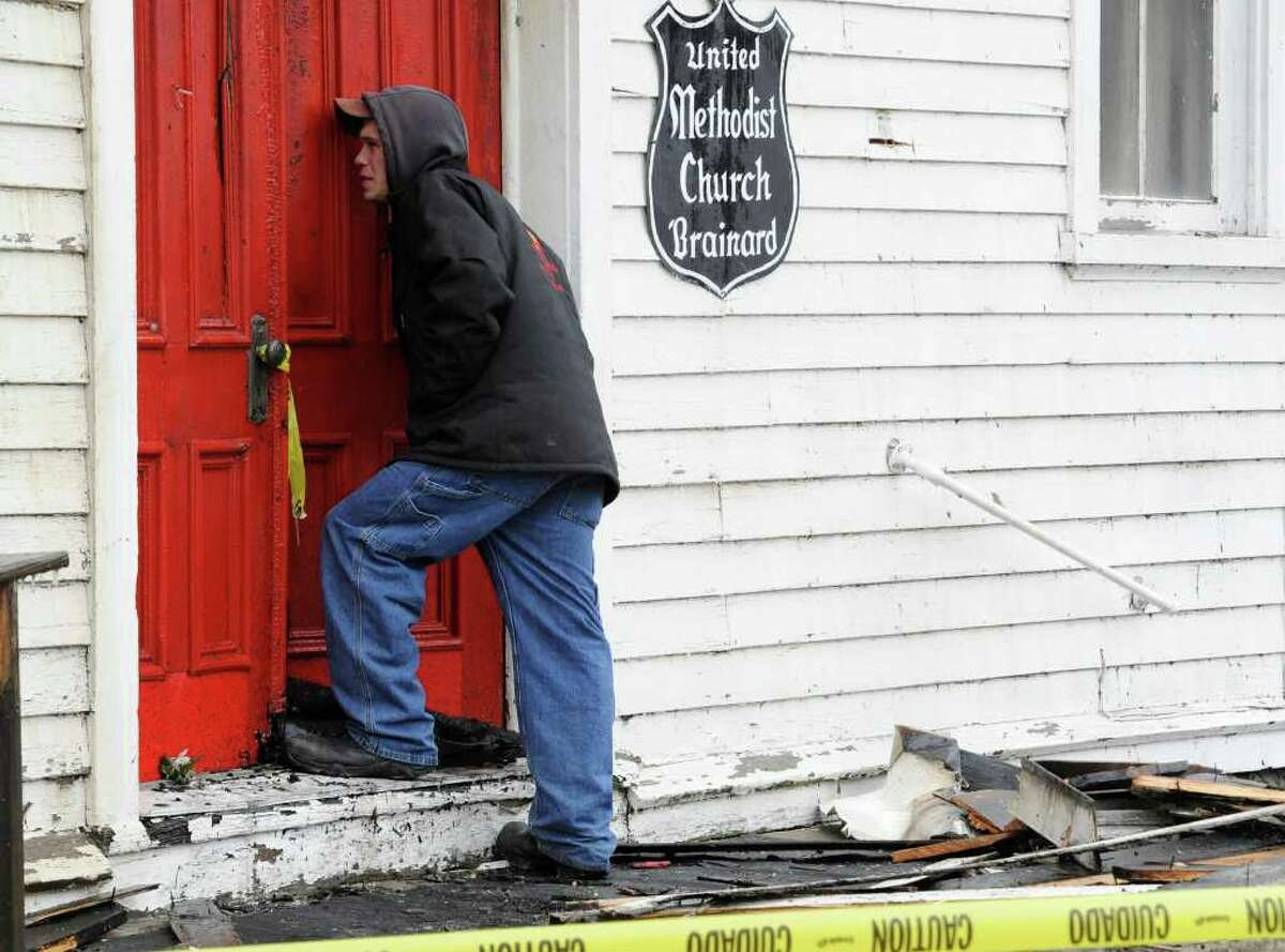 Tsatsawassa Fire Lt. Jay Kreutziger Jr. looks in the front door of the United Methodist Church in Brainard that was gutted by fire on Wednesday, Dec. 22, 2010. (Skip Dickstein / Times Union)