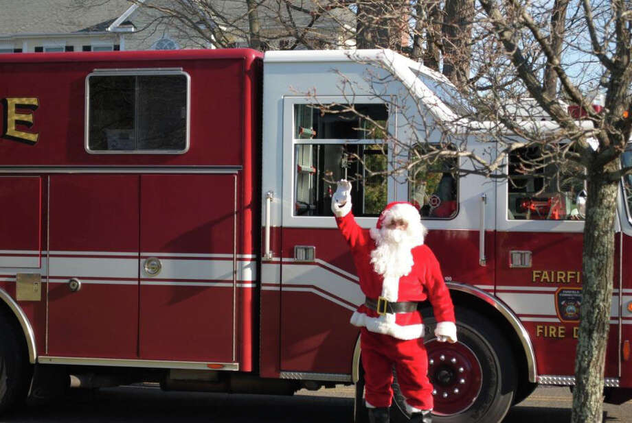Santa Claus gets ready to hop on the Fairfield Fire Fighters Association's MDA Santa Express, delivering toys to local families to raise money for the Muscular Dystrophy Association. This year they raised a record $9,464 Photo: Contributed Photo / Fairfield Citizen