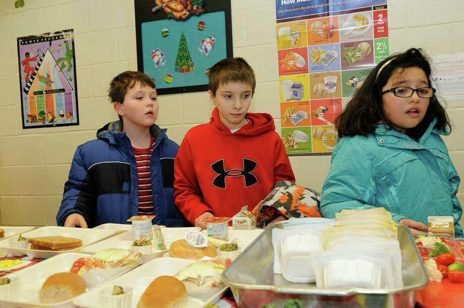 L to R: Thomas Murray, Kenny Hine, and Allison Benitez peruse the healthy lunch choices, including a quinoa and kale quiche, as Holland Hill School participates in a contest to create healthy school lunches in Fairfield, CT on Wednesday, December 22, 2010. The nationwide contest is sponsored by the USDA and the first lady, Michelle Obama. Photo: Shelley Cryan / Shelley Cryan freelance; Fairfield Citizen News freelance