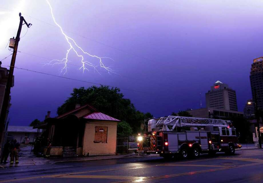 Lightning strikes over a vacant home that was believed to have been struck by lightning according to firefighters from Station No. 3 on the scene at Camaron and Travis near downtown on Wednesday, June 2, 2010.  Photo: KIN MAN HUI, SAN ANTONIO EXPRESS-NEWS / kmhui@express-news.net