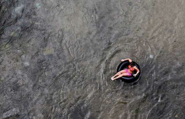 Rain drops fall on a solitary individual floating in the Comal River in Prince Solms Park on Labor Day in New Braunfels, Texas on Monday, Sept. 6, 2010. Photo: KIN MAN HUI, SAN ANTONIO EXPRESS-NEWS / San Antonio Express-News