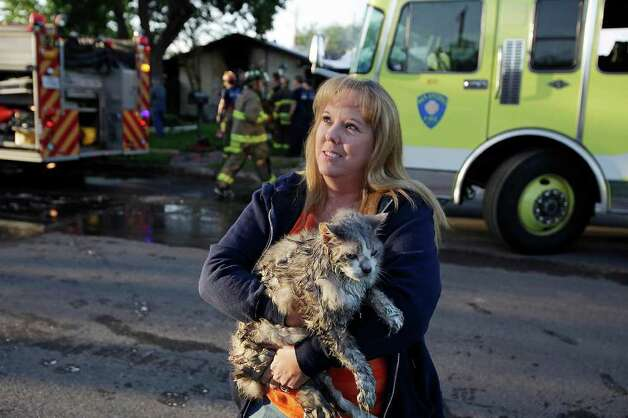 Linda Boubel carries Teka after it was rescued from her brother-in-laws house by San Antonio firefighters at the 400 block of Tidewind Boulevard, Monday, April 19, 2010. Emergency personnel responded to the structure fire at 6:40 a.m. on the city's south side. The fire causes significant damage to the house. The owners of the house were out of town. Photo: JERRY LARA, SAN ANTONIO EXPRESS-NEWS / glara@express-news.net