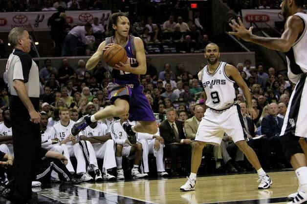 Phoenix Suns Steve Nash keeps the ball in play as San Antonio Spurs Tony Parker, center right, and Tim Duncan defend in the first half of game 4 of seven series in the Western Conference Semifinals at the AT&T Center, Sunday, May 9, 2010. Photo: JERRY LARA, SAN ANTONIO EXPRESS-NEWS / glara@express-news.net