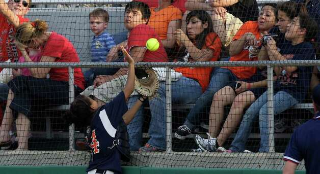 The crowd reacts as the ball gets too close for comfort while Brandeis Broncos catcher Taylor Johnson attempts to catch  a foul ball in Class 5A Softball Regional Quarterfinals Playoff against the Taft Raiders at Northside Softball Fields, Thursday, May 13, 2010. Photo: JERRY LARA, SAN ANTONIO EXPRESS-NEWS / glara@express-news.net