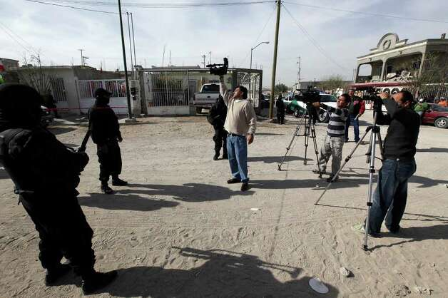 Federal Police keep media members away from a crime scene where four municipal police officers were shot dead in Ciudad Juarez, Mexico, Saturday, Dec. 4, 2010. The media operates in groups when covering breaking news involving the drug cartels. They face pressure not only from those groups but also from the law enforcement that is sometimes involved in the trade. Photo: JERRY LARA, SAN ANTONIO EXPRESS-NEWS / glara@express-news.net