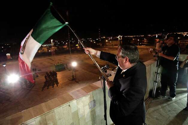 "Ciudad Juarez, Mexico Mayor Jose Reyes Ferriz, waves the flag over an empty city hall parking lot during the celebration of ""El Grito,"" Wednesday, Sept. 15, 2010. The country was celebrating the bicentennial of its fight for independence but due to rampant and out of control violence in Juarez, the mayor decided to televise the event and not allow the public to congregate in the area. The violence comes from the drug war raging throughout the country. Photo: JERRY LARA, SAN ANTONIO EXPRESS-NEWS / glara@express-news.net"