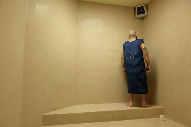 A Bexar County Jail inmate looks away from the camera while wearing a safety smock in the mental health unit, Thursday, July 29, 2010. The smock is used by to keep mentally ill inmates from hurting themselves. Photo: JERRY LARA, SAN ANTONIO EXPRESS-NEWS / glara@express-news.net