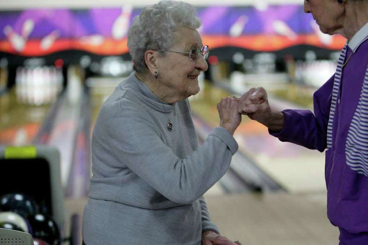 METRO - Bowler Helen Borosh high-fives Edna Stappenbeck as she celebrates her 98th birthday with a cake and members of the Golden 55 Senior Bowling League at the AMF Country Lanes, Thursday, Jan. 28, 2010. JERRY LARA/glara@express-news.net