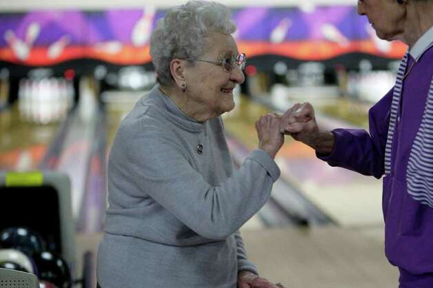 Bowler Helen Borosh high-fives Edna Stappenbeck as she celebrates her 98th birthday with a cake and members of the Golden 55 Senior Bowling League at the AMF Country Lanes, Thursday, Jan. 28, 2010. Photo: JERRY LARA, SAN ANTONIO EXPRESS-NEWS / glara@express-news.net