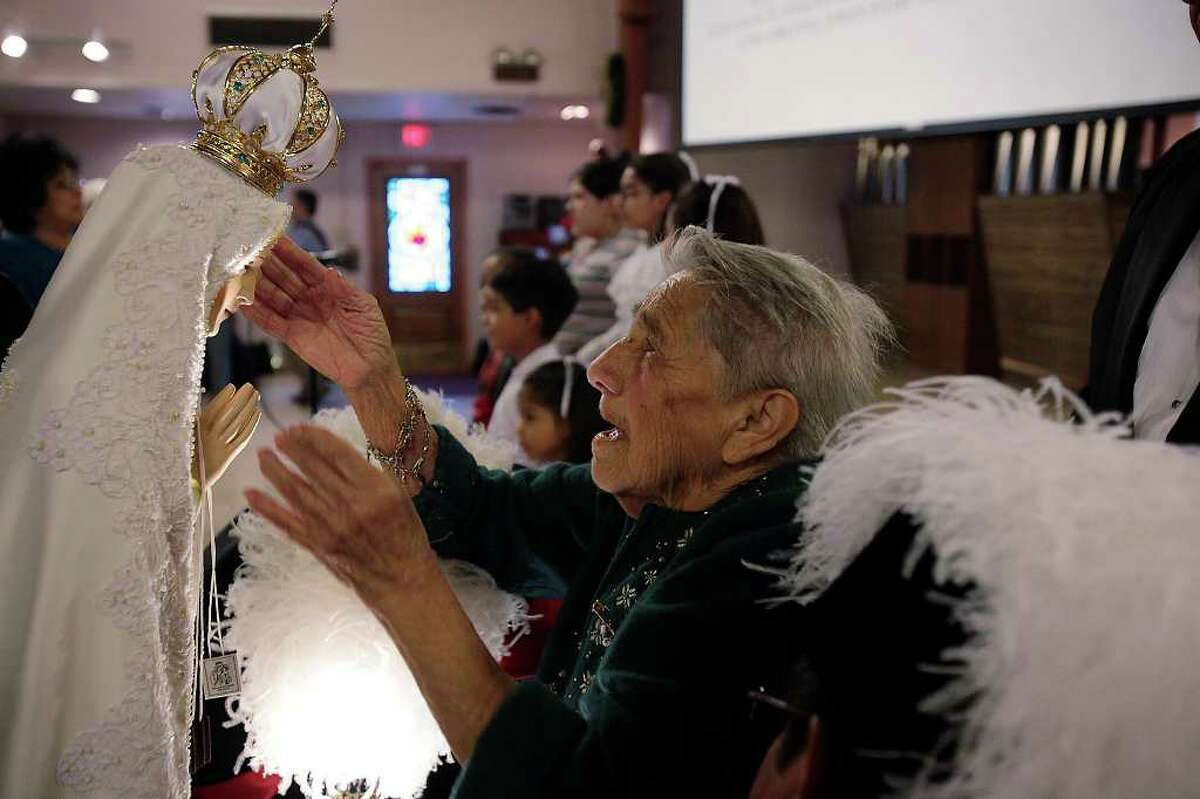 METRO - Angelita Lopez, 85, places the crown on a four-foot icon of Our Lady of Fatima during its arrival at Our Lady of Perpetual Help on the city's eastside, Sunday, Jan. 3, 2010. JERRY LARA/glara@express-news.net