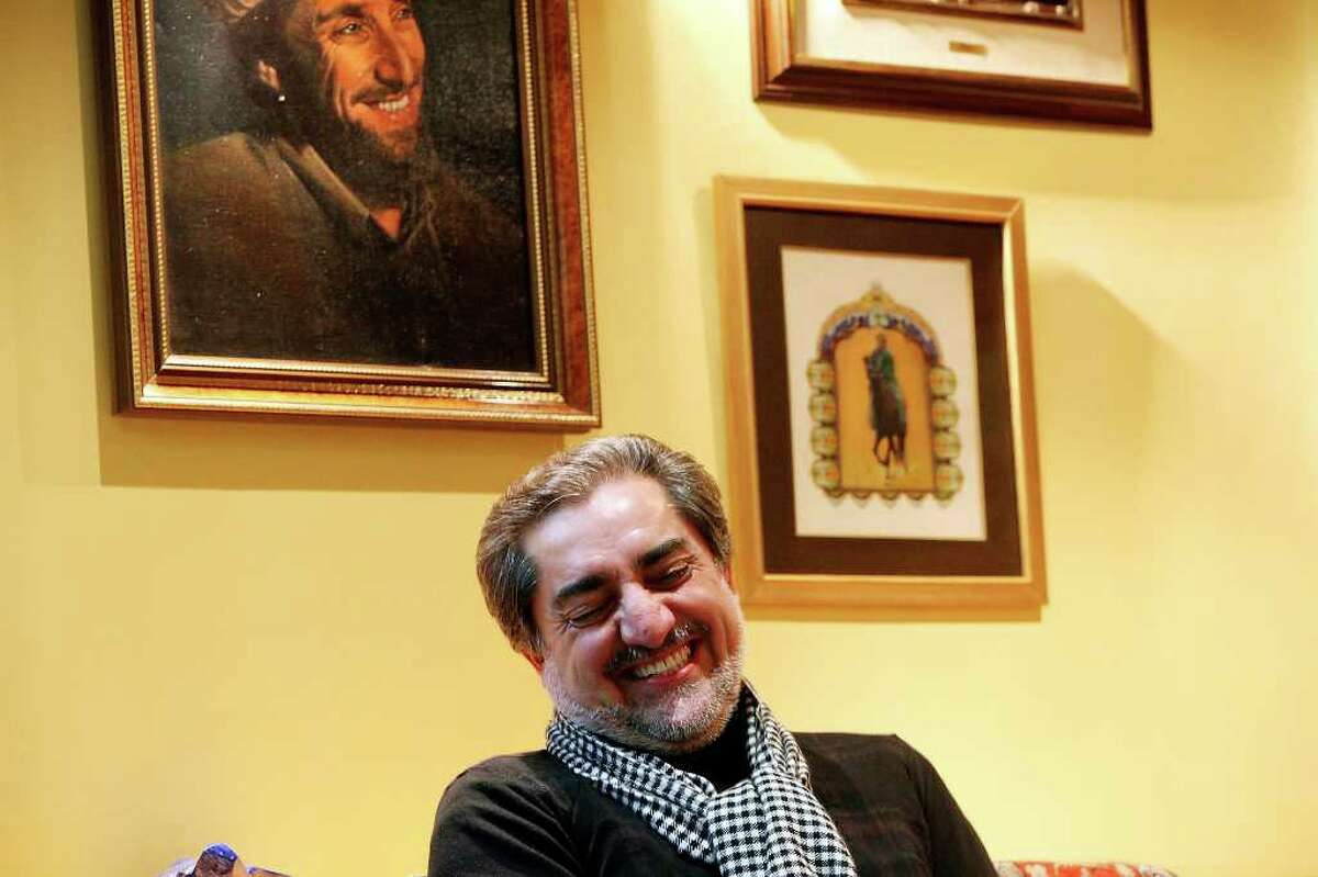 FOR METRO - Former Afghan presidental candidate Dr. Abdullah Abdullah laughs during an interview near a painting of Ahmad Shah Massoud at his home Wednesday Jan. 6, 2010 in Kabul, Afghanistan. Dr. Abdullah was part of the mujahideen freedom fighters with Massoud during the Soviet occupation of Afghanistan. Massoud was assassinated by suicide bombers two days prior to Sept. 11, 2001. PHOTO BY EDWARD A. ORNELAS/eaornelas@express-news.net)