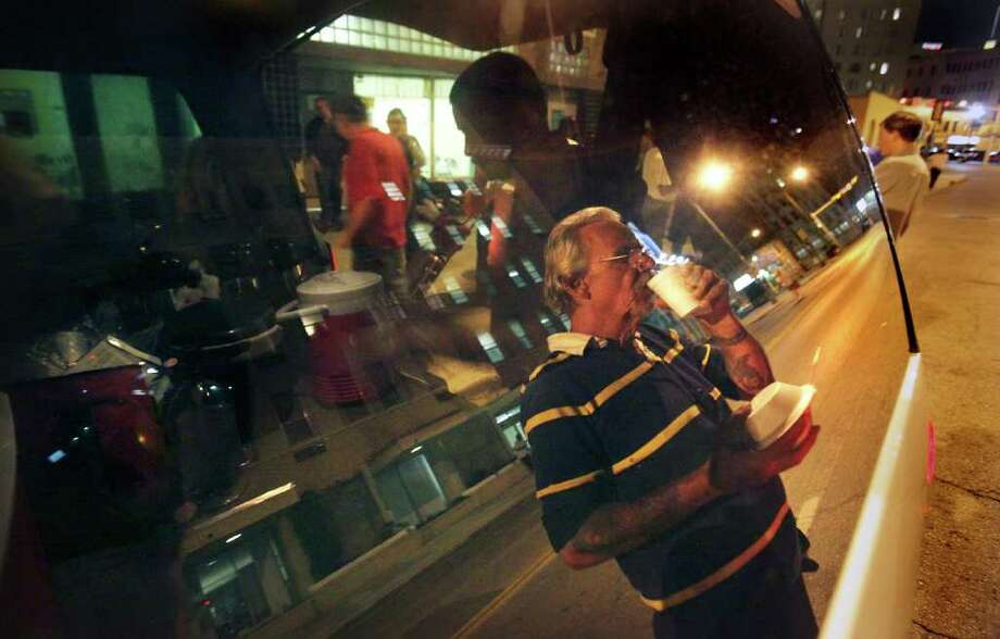 Metro adv - Homeless John Wagener, reflected on the side window of a van and also known as Grandpa on the streets, sips a coffee after he gets a meal from street minister Brian Wicks, in front of the Community Ministries Center on Alamo Street. Tuesday, May 18, 2010. Photo BOB OWEN/rowen@express-news.net Photo: BOB OWEN, SAN ANTONIO EXPRESS-NEWS / SAN ANTONIO EXPRESS-NEWS