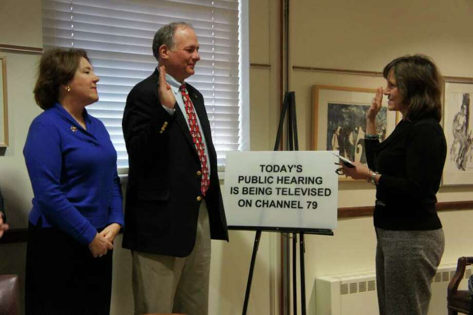 Charles Haberstroh is sworn in as selectman by Town Clerk Patty Strauss, right, on Wednesday, Dec. 22, 2010, while his wife, Patty Haberstroh, left, looks on. Photo: Paul Schott / Westport News