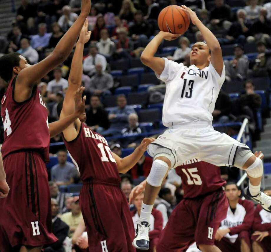 Connecticut's Shabazz Napier, right, takes a jump shot as Harvard's Keith Wright, left, and Brandyn Curry (10) defend during an NCAA college basketball game at Hartford, Conn., Wednesday, Dec. 22, 2010.  (AP Photo/Bob Child) Photo: AP