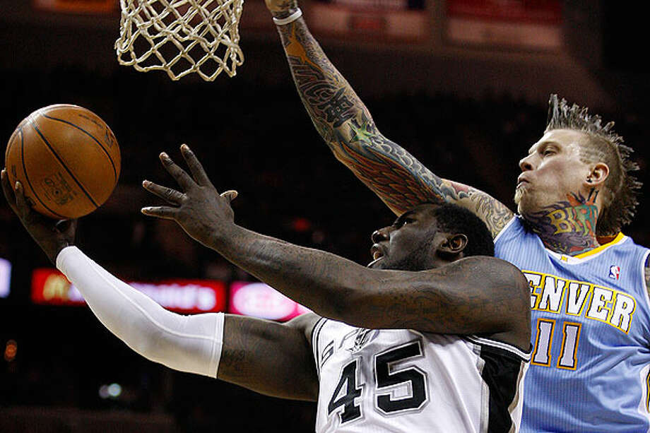 The Spurs' DeJuan Blair goes under the net under pressure from the Nuggets' Chris Andersen during the first half at the AT&T Center, Wednesday.