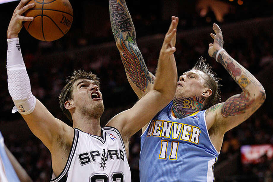 The Spurs' Tiago Splitter drives through the Nuggets' Chris Andersen during the second half at the AT&T Center, Wednesday. The Spurs won 109-103. Photo: JERRY LARA/glara@express-news.net