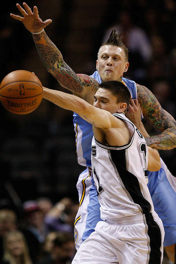 The Spurs' Chris Quinn steals a pass intended for the Nuggets' Chris Andersen during the second half at the AT&T Center, Wednesday. The Spurs won 109-103. Photo: JERRY LARA/glara@express-news.net