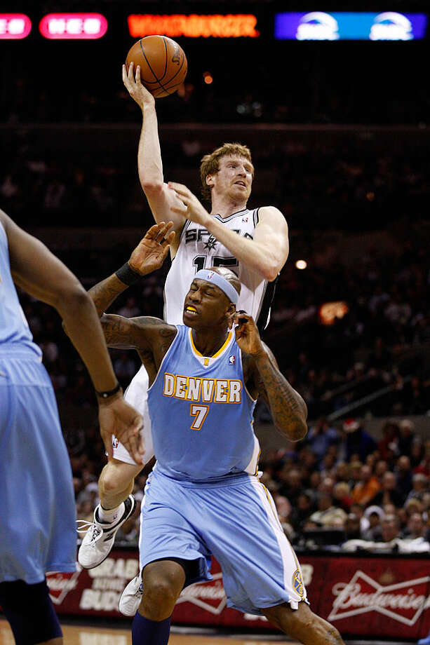 The Spurs' Matt Bonner goes over the Nuggets' Al Harrington during the second half at the AT&T Center, Wednesday. The Spurs won 109-103. Photo: JERRY LARA/glara@express-news.net