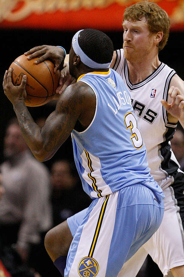 The Spurs' Matt Bonner ties up the Nuggets' Ty Lawson who is then called for tavelling during the first half at the AT&T Center, Wednesday. The Spurs went on to win 109-103. Photo: JERRY LARA/glara@express-news.net