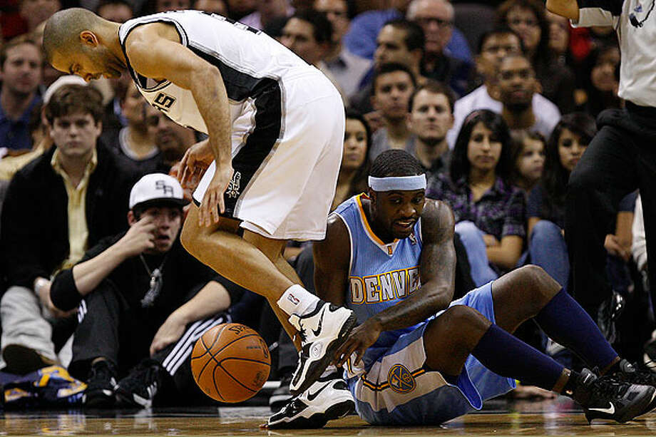 The Spurs' Tony Parker tries to control the ball after he attempted to steal it from the Nuggets' Ty Lawson during the first half at the AT&T Center, Wednesday. The Spurs won 109-103. Photo: JERRY LARA/glara@express-news.net