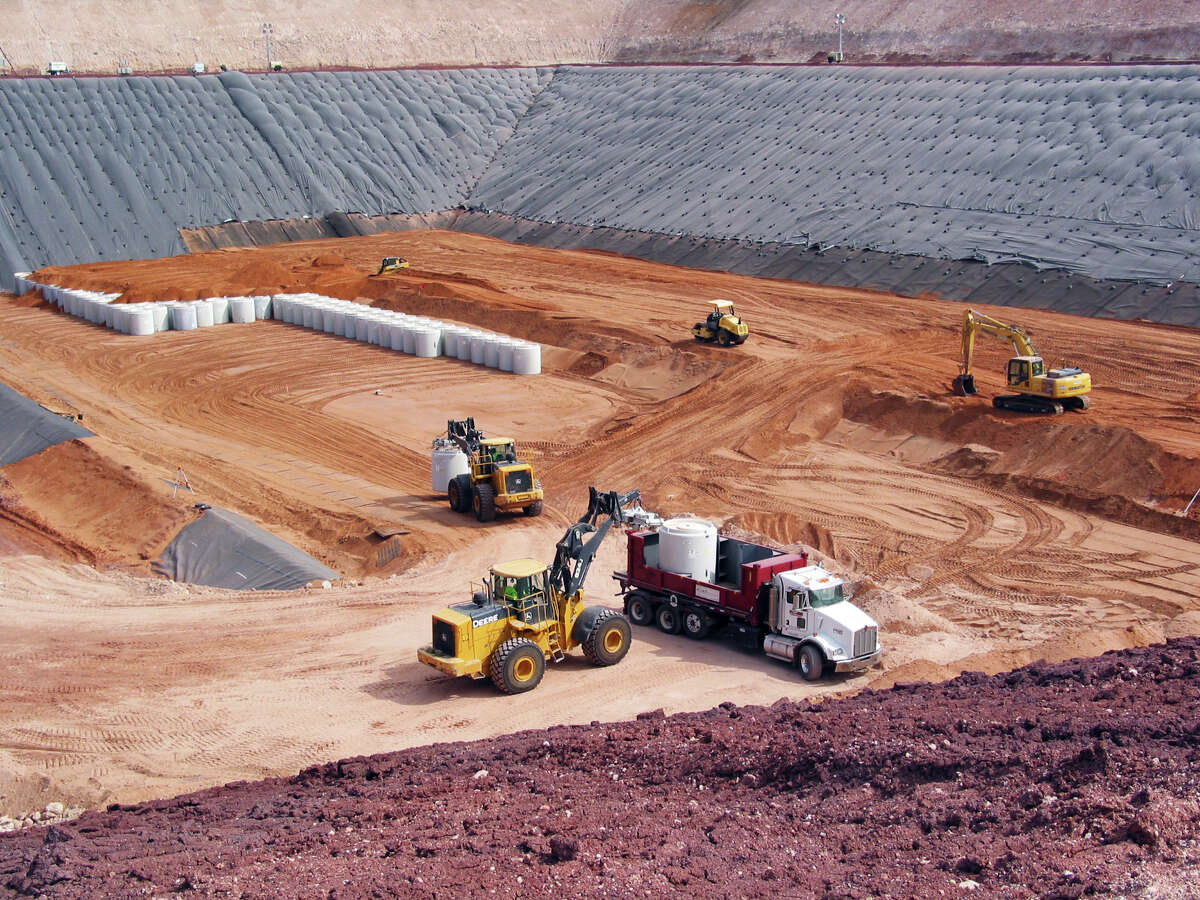 Canisters filled with uranium byproduct waste are placed into a burial pit at the Waste Control Specialists site near Andrews.