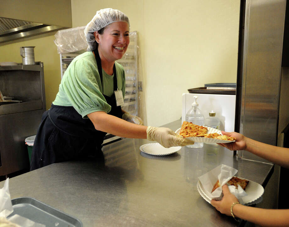 Hilda Walter, a volunteer in the kitchen at Family Violence Prevention Services, serves a meal. The group offers on-site counseling, transitional housing programs and legal services. Photo: BILLY CALZADA/gcalzada@express-news.net / SAN ANTONIO EXPRESS-NEWS