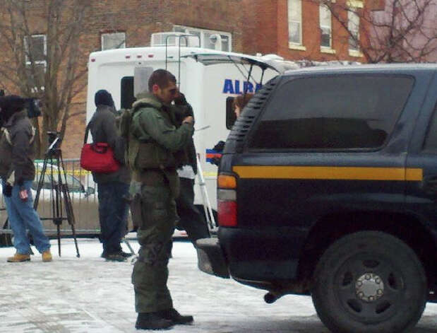 A member of the State Police SWAT team stands vigil near the scene of a hostage situation Thursday morning on Westerlo Street in Albany. (Dayeline Roman / Times Union)