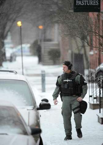 Albany Police SWAT team member Ken Koontz works the radio at the scene of a hostage situation Thursday morning on Westerlo Street in Albany. (Skip Dickstein / Times Union) Photo: SKIP DICKSTEIN