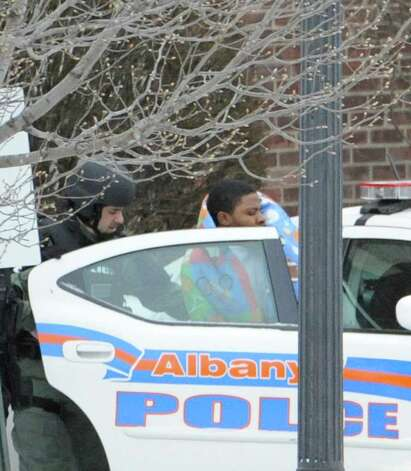 Albany Police SWAT escort a man from 57 Westerlo St. into a police car. (Skip Dickstein / Times Union) Photo: SKIP DICKSTEIN