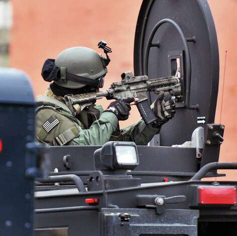 A state trooper armed with an assault rifle covers the scene of a hostage situation Thursday on Green Street in Albany.  (John Carl D'Annibale / Times Union) Photo: John Carl D'Annibale