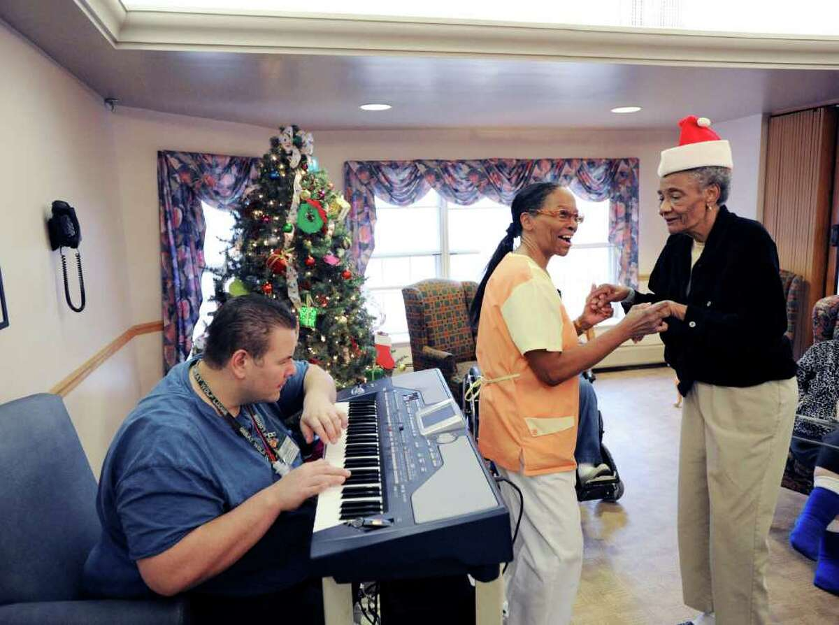 Mike Rinaldi plays the keyboard as nursing assistant Marcia Hudson, center, dances with Alzheimer's patient Rose Desire, right, during an afernoon of rock 'n' roll music at Greenwich Woods Rehabilitation & Health Care Center, Wednesday afternoon, Dec. 22, 2010. Rinaldi is co-director of Recreation at Greenwich Woods.