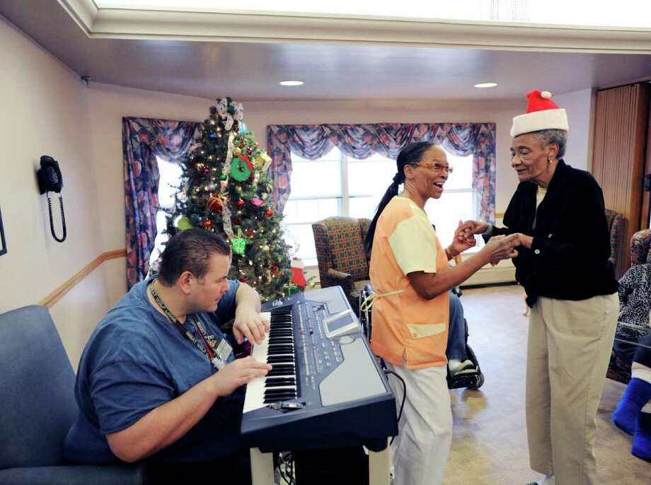Mike Rinaldi plays the keyboard as nursing assistant Marcia Hudson, center, dances with Alzheimer's patient Rose Desire, right, during an afernoon of rock 'n' roll music at Greenwich Woods Rehabilitation & Health Care Center, Wednesday afternoon, Dec. 22, 2010.  Rinaldi is  co-director of Recreation at Greenwich Woods. Photo: Bob Luckey / Greenwich Time