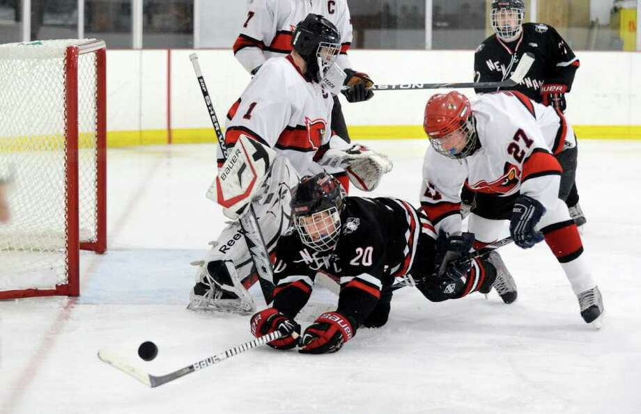 PT Prins of New Canaan High School, # 20, center, gets checked to the ice by Craig Macken, # 27 of Greenwich High School, right, as GHS goalie Ricky Piper, left,  looks for the puck during second period action of hockey game between Greenwich High School vs. New Canaan High School at Hamill Rink, Byram, Thursday night, Dec. 23, 2010. Photo: Bob Luckey / Greenwich Time