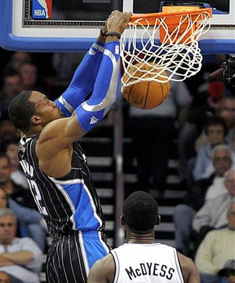 Magic center Dwight Howard (left) dunks the ball over Spurs center Antonio McDyess on Thursday in Orlando. Photo: Phelan M. Ebenhack/Associated Press