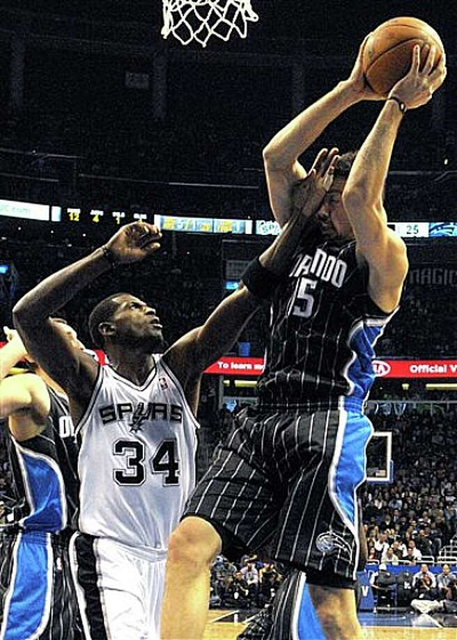 Magic forward Hedo Turkoglu (right) is hit in the face by Spurs center Antonio McDyess while fighting for a rebound on Thursday in Orlando. Photo: Phelan M. Ebenhack/Associated Press