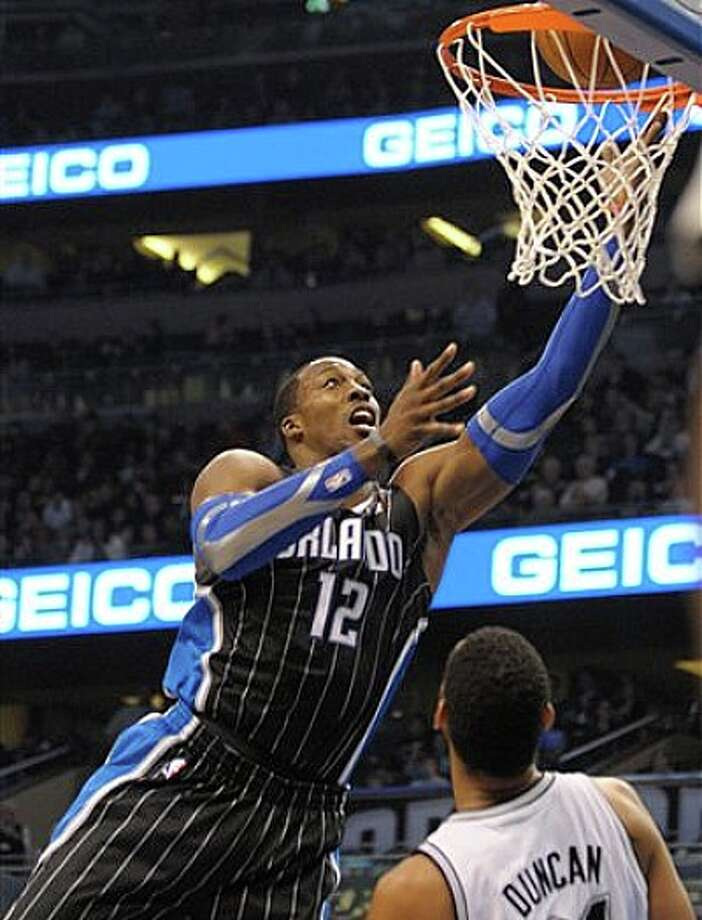 Magic center Dwight Howard (left) puts up a shot in front of Spurs center Tim Duncan on Thursday in Orlando. Photo: Phelan M. Ebenhack/Associated Press