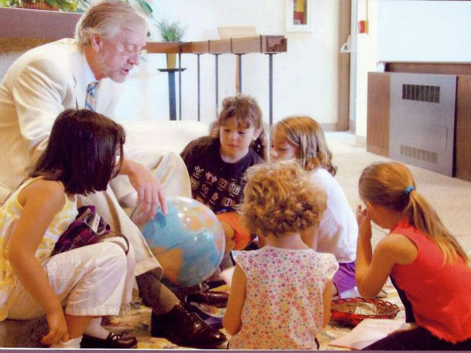 Rev. Edward C. Horne of the United Methodist Church of Westport and Weston discusses the globe with children of the congregation. Photo: Contributed Photo / Westport News