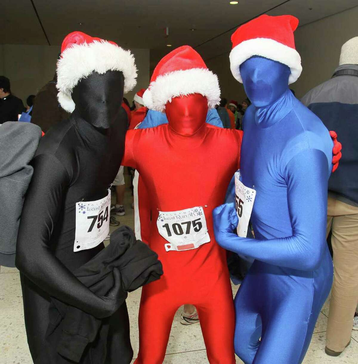 From left: Sean Reynolds, Ryan Bellinger and Connor Devine wear full-body suits and Santa hats to stay warm while running in Albany?s Last Run 5K. (Joe Putrock / Special to the Times Union)