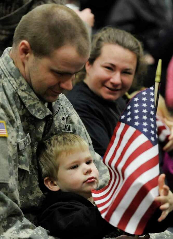 The Barrow family -- father, Joseph; mother, Amy; and Dylan, 3 -- wait at the National Guard Armory in Queensbury for the annual march to support the men and women who are away from their families during the holidays.  (Skip Dickstein / Times Union) Photo: Skip Dickstein