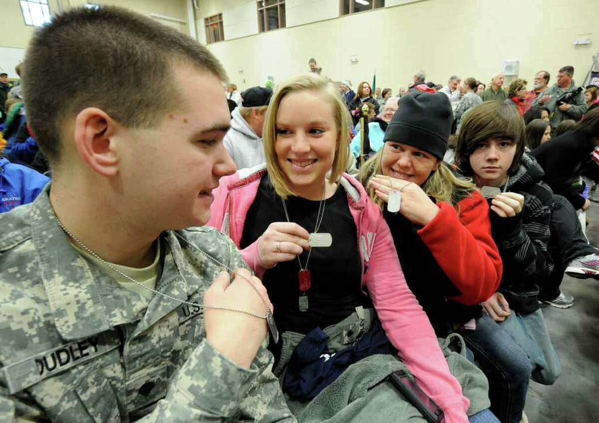 Spc. Adam Dudley, Kaileih Whittaker, Patty Bills and Adam Bills show dog tags with the names of service members in the Middle East at the National Guard Armory in Queensbury on Dec. 24, 2010, as they prepare for the annual march to support the troops during the holidays. (Skip Dickstein / Times Union)