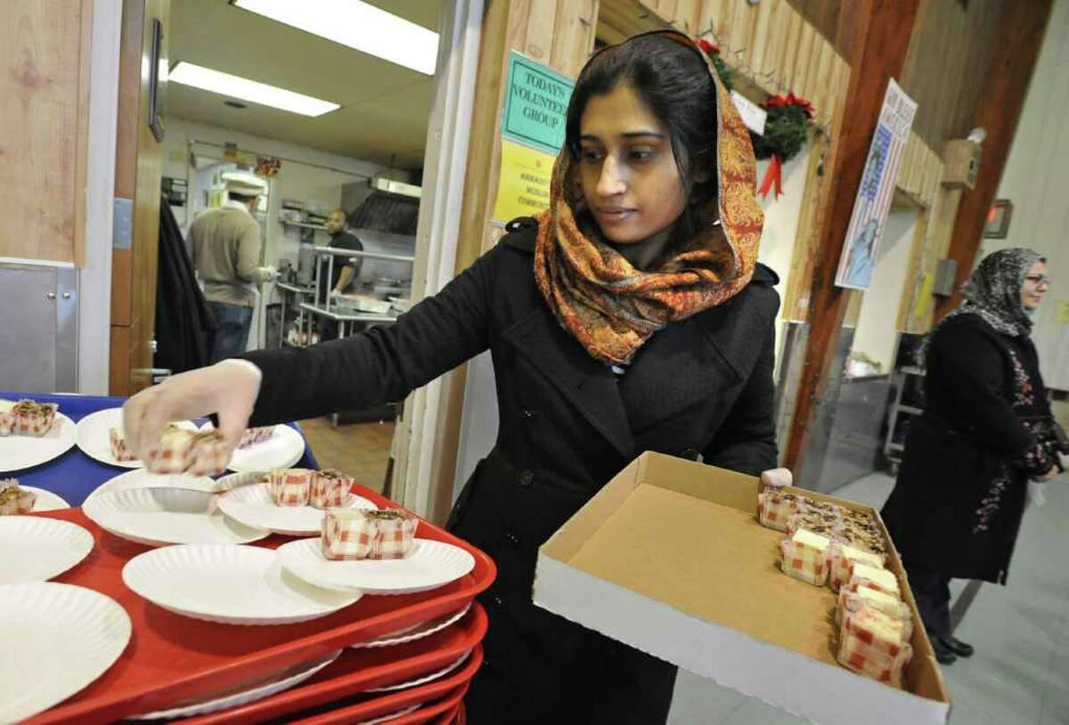 Humaira Asim of Colonie puts cheesecake squares on plates at the Salvation Army soup kitchen in Schenectady on December 24, 2010. Members of the local Ahmadiyya Muslim community helped the Salvation Army staff during the busy preparation of the holiday meal on Christmas Eve. (Lori Van Buren / Times Union)