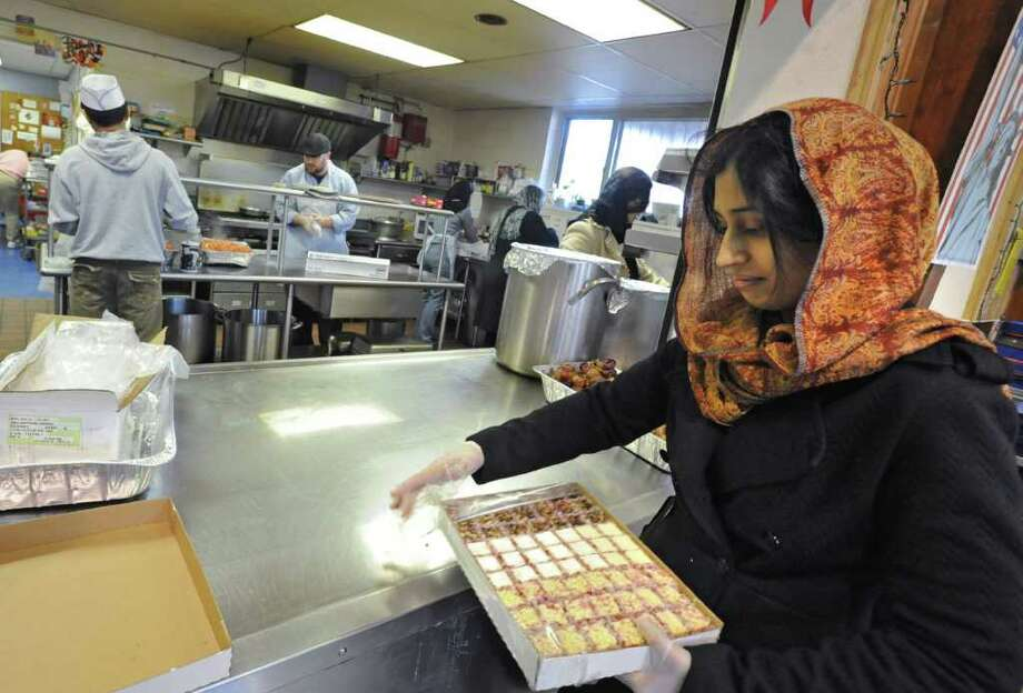 Salvation Army workers work in the background as Humaira Asim of Colonie puts cheesecake squares on plates at the Salvation Army soup kitchen in Schenectady on December 24, 2010. Members of the local Ahmadiyya Muslim community helped the Salvation Army staff during the busy preparation of the holiday meal on Christmas Eve.  (Lori Van Buren / Times Union) Photo: Lori Van Buren