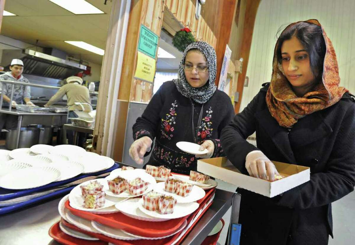 Tahira Khan of Glenville, left, and Humaira Asim of Colonie put cheesecake squares on plates at the Salvation Army soup kitchen in Schenectady, NY, on December 24, 2010. Members of the local Ahmadiyya Muslim community helped the Salvation Army staff during the busy preparation of the holiday meal on Christmas Eve. (Lori Van Buren / Times Union)